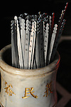Bao-jhong Yi-min Temple, Kaohsiung -- These metal sticks are called 'qian' (also transliterated as 'chian' or 'chien') in Chinese.<br /> <br /> The Taoist believer asks the gods a question in prayer, then shakes the urn with the sticks inside until one of them sticks out higher than the others. This is the 'qian' that gives him the answer of the gods.<br /> <br /> He shows the 'qian' to a  monk at the temple who will fetch a corresponding piece of paper with an ancient text on it from a cabinet. The monk proceeds to explain the writing on the paper and interprets its meaning and the gods' answers.
