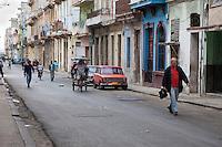 Cuba, Havana.  Early Morning Central Havana Street Scene.  Pedestrians, Bicycle Taxi.
