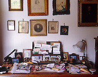 This desk is cluttered with old family photographs and mementos