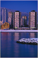 Condominium towers of the West End and the Tree of Lights on English Bay, at twilight after a light snowfall, from Vanier Park in Kitsilano, Vancouver, BC.