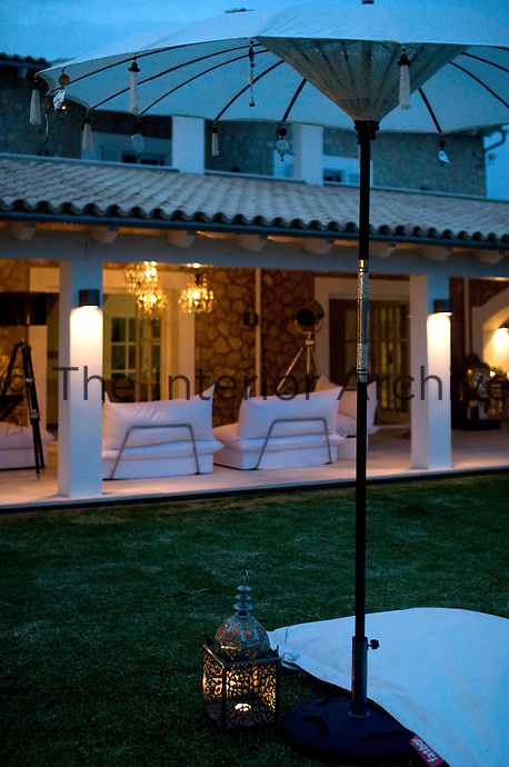 As night falls, the garden and covered terrace are transformed, with seating areas bathed in warm light from candles, chandeliers and lanterns