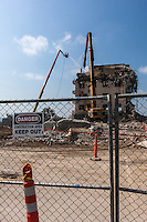 "A ""Danger - Keep Out"" sign hangs on a chain link fence in the foreground while, in the background, crews work at demolishing the old hospital, recently replaced by the new Eden Medical Center, in Castro, Valley, California."