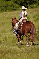 Ranch hand on horseback riding away