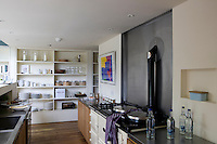 Open shelves line one wall of the kitchen whilst the alcove behind the Aga is lined with brushed steel