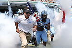 07 September 2013: UNC head coach Larry Fedora and player Dan Mastromatteo (holding flag) lead the team onto the field before the game. The University of North Carolina Tar Heels played the Middle Tennesse State University Blue Raiders at Keenan Stadium in Chapel Hill, NC in a 2013 NCAA Division I Football game. UNC won the game 40-20.