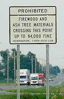 A sign marks the boundary and fines for removing Ash tree materials from a restricted area in northwest Ohio where the Ash Borer beetle infestation continues. The trees are being destroyed by the ash borer beetle, an invasive species of beetle thought to have brought into the country from China in wooden pallets used to carry imported goods. The beetle kills the trees by boring under the bark.<br />
