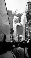 USA. NYC. 9/11/2001. Pedestrians run from falling debris as second tower of the World Trade Center collapses after terrorist attack.