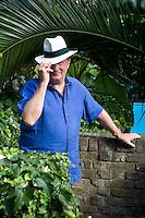 Portrait of Rupert Cavendish wearing a Panama hat in his garden