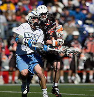 Michael Kimmel (15) of Johns Hopkins has the ball checked away from him by John Cunningham (3) of Princeton during the Face-Off Classic in at M&T Stadium in Baltimore, MD