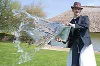 Man wearing traditional clothes splashes a buckets of water as part of the fertility traditions during the Easter watering celebration in the Skansen open air ethnographic museum in Szenna (about 200 km South-West of capital city Budapest), Hungary on April 14, 2017. ATTILA VOLGYI