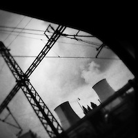 Smoking cooling towers of the Prunéřov I coal-fired power plant seen from the train passing through the industrial area in the north of the Czech Republic, 4 September 2013. The whole nothern region of the country constantly suffers environmental impacts from the coal mining and the coal-fired energy production.