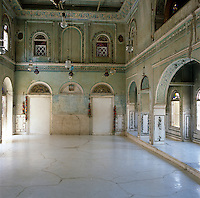 The shabbily grand entrance hall to the Jaipur apartment  has intricate fanlights and traditional wall tiles