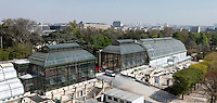 Jardin des Plantes, Museum National d'Histoire Naturelle, Paris, France. Aerial view of the Jardin des Plantes showing the Glasshouses in the afternoon light, left to right: Incubators, restored 1995-97, Paul Chemetov and Borja Huidobro; Plant History Glasshouse (formerly Australian Glasshouse), 1830s, Rohault de Fleury; New Caledonia Glasshouse (formerly Mexican Hothouse), 1834, Charles Rohault de Fleury; Tropical Rainforest Glasshouse (formerly Le Jardin d'Hiver or Winter Gardens), 1936, René Berger,  and alongside it the Desert and Arid Land Glasshouse, 1930s; in the background is the Paris skyline.