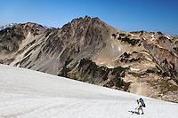 Backpacker climbing snow slope below Pulitzer Peak, Bailey Range Traverse, Olympic Mountains, Washington