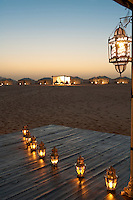 A row of lanterns on the deck of the desert camp restaurant with the bedroom tents illuminated in the distance