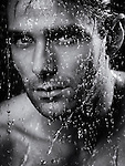 Dramatic closeup portrait of a man face wet from water pouring on it. Black and white.