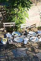 The remants of a summer lunch on a table on the terrace