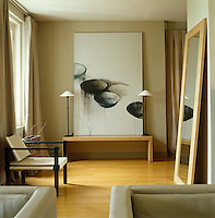 In the living room of a house in Normandy the muted tones of beige and natural wood have allowed the large painting at one end to become the focal point of the space