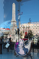 The Praca dos Restauradores, or Restauradores Square, celebrating the restoration of Portuguese independence in 1640, with the obelisk, 1886, with the names and dates of the battles of the Portuguese Restoration War, seen reflected in the window of a musical instrument shop, Lisbon, Portugal. Picture by Manuel Cohen