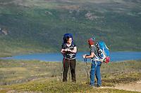 Female hikers take break with lake Abeskojavri - Abiskojaure in background, Kungsleden trail, Lapland, Sweden
