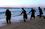 Ultra-orthodox Jewish men avoid the approaching water, as they visit the beach of the Israeli outpost of Shirat Hayam, in the settlement bloc of Gush Katif, Gaza Strip. A growing number of ultra-orthodox Jews support the settlers' struggle against the planned pullout from Gaza. May 3, 2005.