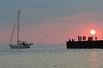Sailboat Leaving Bayfield Marina with People on Pier Silhouetted against Sun (Landscape)