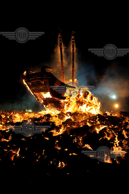 A huge model boat is burned on a pyre of paper money on the  beach at Baisha Port, the culmination of a festival, that takes place every third year, honouring the island's gods. During the previous week a it was carried, in procession, around the island and now the boat burns in front of a crowd many of whom have come from the main island or even from overseas.