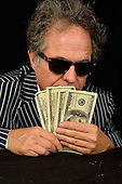 Stock photo of a greedy man with money and sunglasses