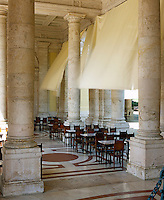 Curtains, which provide shade form the hot Tuscan sun, billow in the wind above the marble topped tables of the cafe