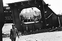 India. Province of Gujarat. Alang. Workers and a huge scrap's piece on the beach. Ships aground. Vessels stranded. Bottoms of ships at low tide on the shore. Alang is located in the Gulf of Khambhat and is a ships breaking place. Alang, located in the Gulf of Khambhat, is a ships breaking place and is considered as the biggest scrapyard in the world. Ships recycling for its metals. Environmental issues. Hazardous waste. © 1992 Didier Ruef