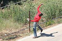 BARI, 1 AGO - Alcune centinaia di immigrati ospiti del Cara di Bari hanno bloccato strade e binari nei pressi del Centro di accoglienza per protesta contro le lungaggini burocratiche che ritarderebbero il rilascio dello status di rifugiati. I migranti hanno bloccato la Statale 16 bis in entrambe le direzioni di marcia e stanno causando disagi alla circolazione dei treni. Sul posto stanno confluendo in numero massiccio le forze dell'ordine. Cancellati dalle Ferrovie dello Stato dieci treni regionali; ritardi per sei convogli a lunga percorrenza. nella foto un immigrato carica la polizia