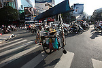 A man pushes a food cart through at a traffic circle in Ho Chi Minh City, Vietnam. July 3, 2011.