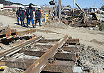 Relief workers walk past the shattered railway station in Tona, Miyagi Prefecture, Japan on  25 March 20011. .Photographer: Robert Gilhooly
