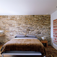 The stone wall is the main focus of this bedroom and influences the palette of its furnishings