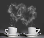 Two cup of steaming aromatic hot coffee with heart shaped steam over gray background. The steam is a realistic computer graphic. Valentines Day love romantic relations conceptual still life photo-illustration.