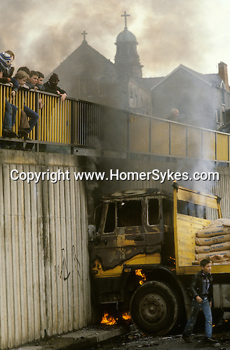 Ireland The Troubles. Derry Londonderry hijacked lorry set on fire by young trouble makers and used as a barricade. 1980s.  The Church behind the burning truck is the Long Tower Roman Catholic Church,  Lecky Road Flyover.