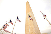 The Washington Monument is shown framed with United States flags blowing in the wind in Washington, DC. The Washington Monument is the most prominent structure, as well as one of the earlier attractions, in Washington, D.C. It was built in honor of George Washington, who led the country to independence and then became its first President. The Monument is shaped like an Egyptian obelisk, stands 555? 5 1/8? tall, and offers views in excess of thirty miles. It was finished on December 6, 1884.