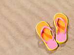 Pair of orange flip flops on beach sand background