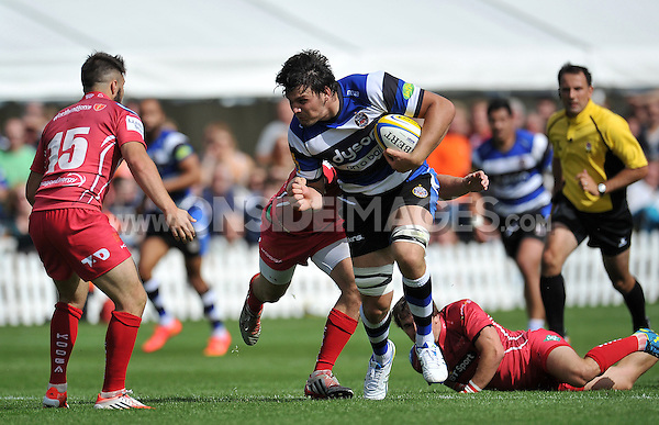 David Sisi takes on the Scarlets defence. Pre-season friendly match, between Bath Rugby and the Scarlets on August 16, 2014 at the Recreation Ground in Bath, England. Photo by: Patrick Khachfe / Onside Images
