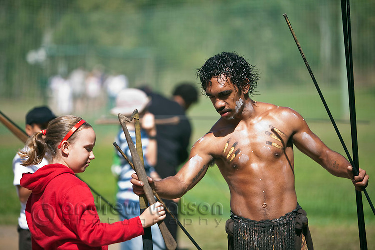 Indigenous guide teaching young tourist how to throw spears at Tjapukai Aboriginal Cultural Park.  Smithfield, Cairns, Queensland, Australia