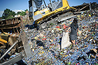 Annie, 11, searching for plastic and metal between two bulldozers at the 'Trash mountain', Makassar, Sulawesi, Indonesia. Many of the pickers follow the bulldozers as they move newly dumped waste, uncovering plastic and metal for recycling in the process.