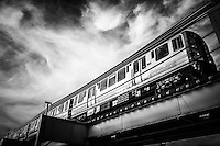 "Photo of Chicago ""L"" elevated train in black and white with swirly clouds."