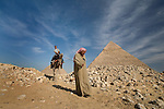 A local Egyptian man leads a male tourist on a camel ride around the site of the Pyramids of Giza near Cairo, Egypt.