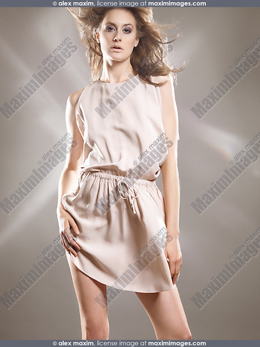 High fashion studio photo of a beautiful woman wearing a beige dress. The photo is not model released, however the model release can be acquired from the modeling agency if necessary. Agency's fees may apply depending on the usage.