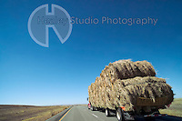 Americana Series: Road Trip<br /> <br /> Overloaded flatbed truck with haybales under stark blue sky