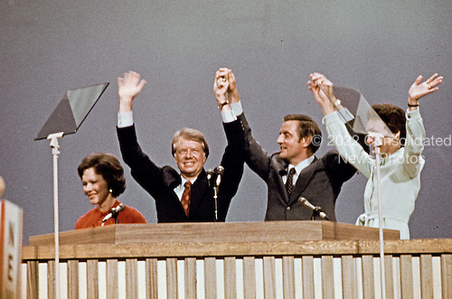 Governor Jimmy Carter (Democrat of Georgia), the 1976 Democratic Party nominee for President of the United States, left center, and US Senator Walter Mondale (Democrat of Minnesota), the 1976 Democratic Party nominee for Vice President of the US, right center, and their wives Rosalynn Carter, left, and Joan Mondale, right, acknowledge the cheers of the delegates following their acceptance speeches at the 1976 Democratic Convention  at Madison Square Garden, New York, New York on July 15, 1976.<br /> Credit: Arnie Sachs / CNP