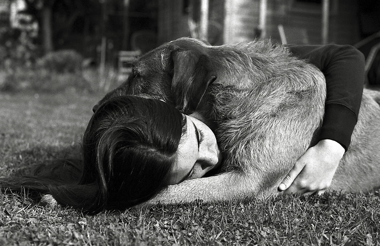 A young woman cuddling her pet dog on the grass