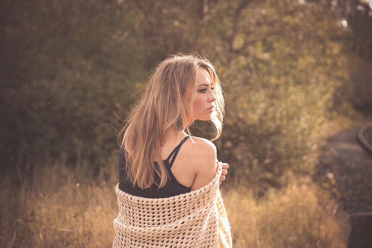A beautiful  young woman with blonde hair standing outside in the nature wearing a long skirt and a crochet stole
