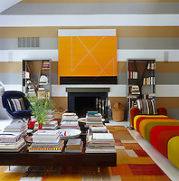 The walls of this contemporary living room have been painted in horizontal stripes and the room furnished using bold colours