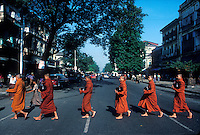 Buddhist monks cross the street on their way to receive offerings of food, in Rangoon (Yangon), Myanmar (Burma).Photo by Owen Franken.